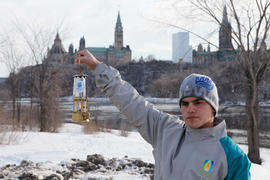 Day 1 flame attendant poses with Paralympic Lantern in front of Parliament Hill in Ottawa, Ont.