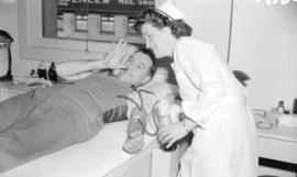 [Portrait of R.J. O'Leary with nurse while donating blood]