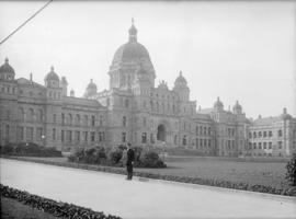Man posing in front of Parliament Buildings in Victoria, B.C.