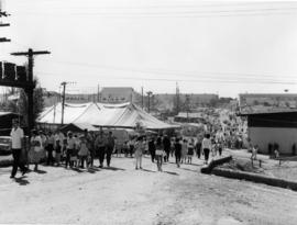 View of crowds and tents on P.N.E. grounds, with Forum, Pure Foods, and Pacific Showmart building...