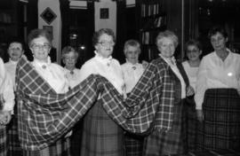 Group of women wearing tartan skirts holding a piece of the Centennial tartan fabric