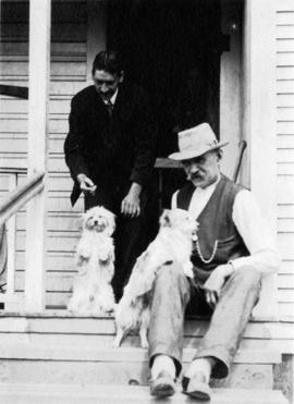 [Two men and dogs on a porch]