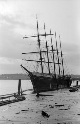 [Partially grounded masted ship in harbour]