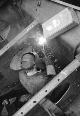 [Welder at work on boat in Burrard Drydock]