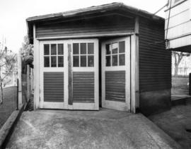 [The doorway to a six-sided structure (garage) beside a house]