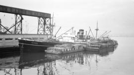 S.S. Trident [at dock, with lumber-filled barges alongside]