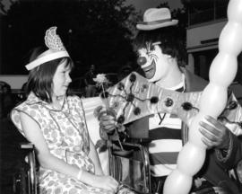 Clown with young girl on P.N.E. grounds