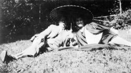 [L.D. Taylor reclining on a lawn with an unidentified woman holding an umbrella]