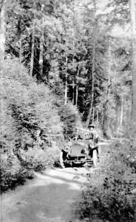 [A man and woman in an open-top car on Capilano Road]