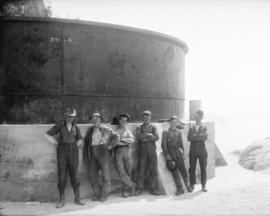 [Men standing outside surge tank of hydraulic tunnel from Buntzen Lake]