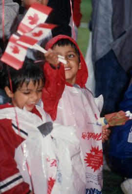 Two children waving Canadian flags during the Centennial Canada Day celebration