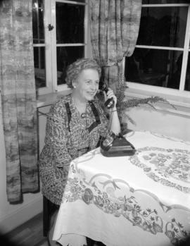 [Woman sitting in her dining room on the first rotary dial telephone in the Cedar Exchange]