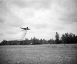 [Water bomber dropping water on a forested area beside a field in Abbotsford]