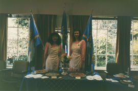 Two women behind food table during Centennial birthday celebrations