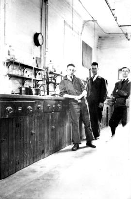 Three laboratory workers: E.F. Shoove, D. Morris, and G. Stevens