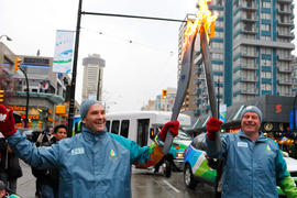 Torchbearer 246 David Johnston (R) passes the flame to torchbearer 247 Graham McLachlan (L) in Va...