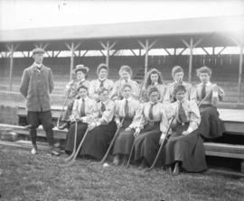 [Women's field hockey team seated near stands at Brockton Point grounds]