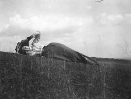 [Woman laying on a hillside, holding her hat on her head]