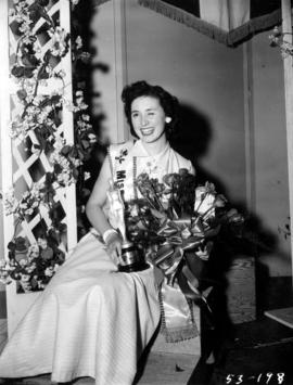 Lynn Adcock posing with flowers and trophy after winning Miss P.N.E. pageant