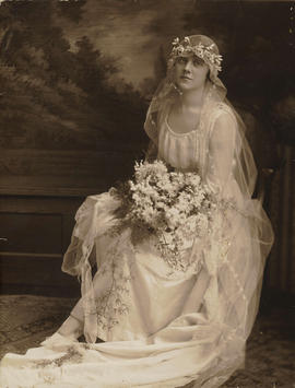 [Studio portrait of Miss Pybus in wedding gown with flowers]