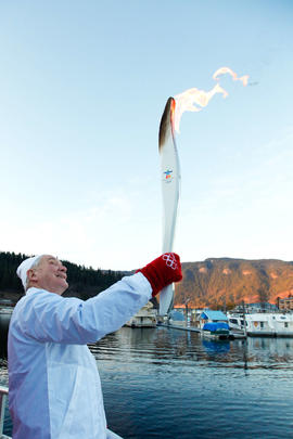 Day 89 Torchbearer 138 Gordon Mackie carries the flame on a houseboat in Sicamous, British Columbia.