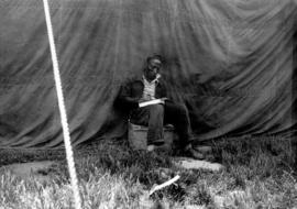 [A man sitting in front of a] Circus [tent writing a letter]