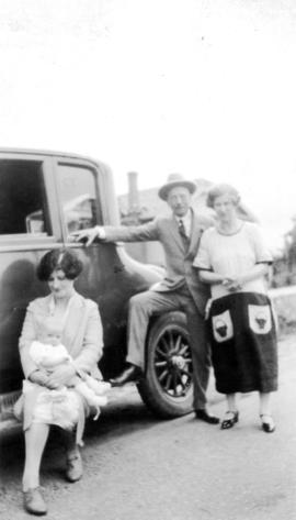 [L.D. Taylor leaning against car with two women and a baby]