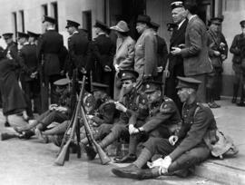 [Soldiers sitting on curb waiting to see King George VI and Queen Elizabeth]