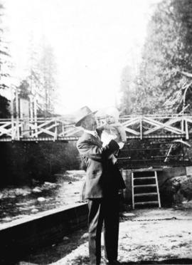[L.D. Taylor holding baby by the Capilano River]
