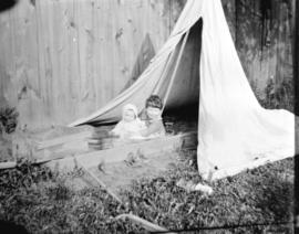 [Two children sitting under a tent in a yard]