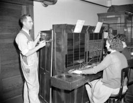 [Man painting a wooden panel beside a switchboard operator at the Mission Telephone Company]
