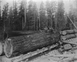 [Four men posing with logs on Great Northern Railway car]