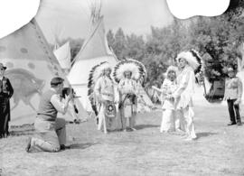 [Stoney Indians posing with baseball bat for photographer at the Calgary Stampede grounds]