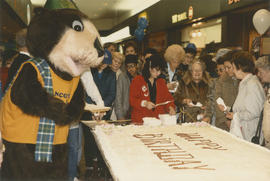 Tillicum cutting birthday cake in a shopping mall