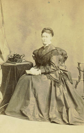 [Studio portrait of woman seated at a table]