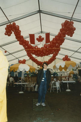 Woman under Canadian flag and decorative balloons inside the Heritage Showcase tent