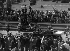 [Crowds cheer and pipers and drummers play as  King George VI and Queen Elizabeth travel by car]