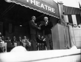 A.E. (Dal) Grauer, president of B.C. Electric Co. and P.N.E. President J.S.C. Moffitt on stage at...