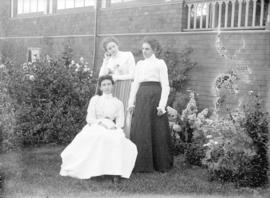 [Mrs. Robert Scott (seated) and two unidentified women assembled outside Scott residence at south...