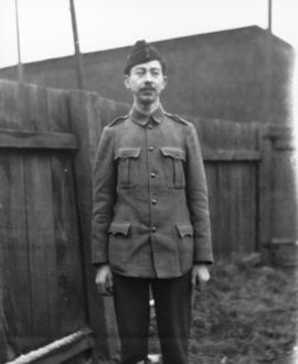 [W. H. B.  in military uniform, standing next to fence]