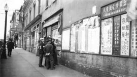 A group of men reading notices posted on a wall in Chinatown