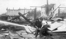 [Two men hosing down the ruins after the fire at Wallace Shipyards]
