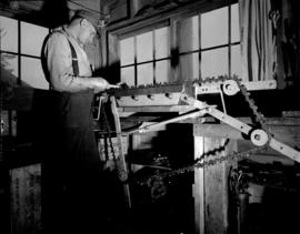 [Man inspecting saw blade at] Pacific Mills [on the] Queen Charlotte Islands