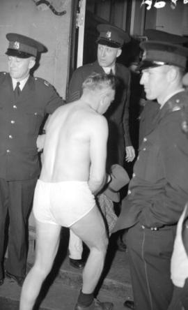 [Doukhobor man, dressed only in his underwear, entering the police station while policemen watch]