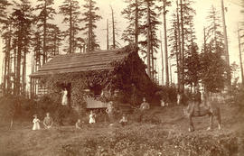 Pioneer cottage with tall trees in background, woman on steps, children and man on horseback in f...