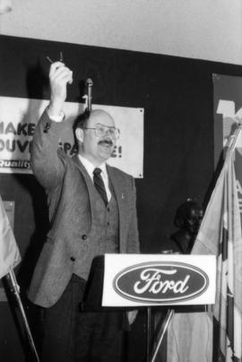 Mike Harcourt holding up Ford keys at podium