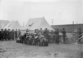 Men lined up on a field next to tents, suitcases in a pile, men in uniform present