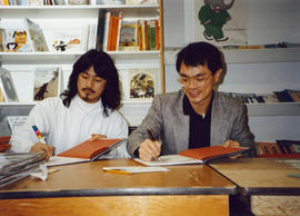 Paul Yee and illustrator Simon Ng signing copies of Tales from Gold Mountain at Children's Book C...