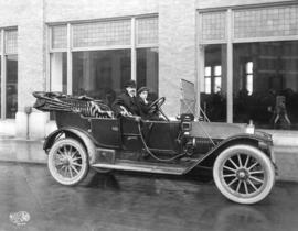 [His Worship T.S. Baxter in a car in front of the Canadian Fairbanks Morse Company warehouse]