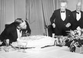 [The Honourable E.W. Hamber blows out the candles on his cake at his birthday dinner]